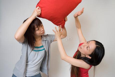 クッションで殴りかかる女性の写真素材 [FYI01940770]