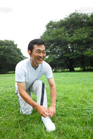 スポーツシューズのひもを結ぶ中年男性の写真素材 [FYI01941679]