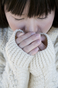 温めるように両手を包む女性の写真素材 [FYI01945937]