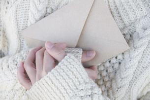 手紙を大事に抱く女性の手の写真素材 [FYI01945994]