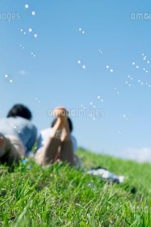 芝生に寝転ぶカップルの後姿とシャボン玉の写真素材 [FYI01946307]
