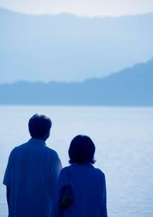 湖を旅行で訪れたシニア夫婦の後姿の写真素材 [FYI01946388]