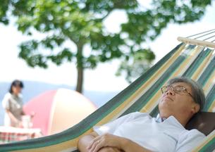 ハンモックに眠るシニア男性と食事の準備をするシニア女性の写真素材 [FYI01946560]