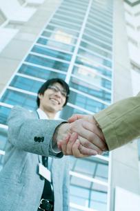 オフィスのロビーで握手をするビジネスマンの写真素材 [FYI01946636]