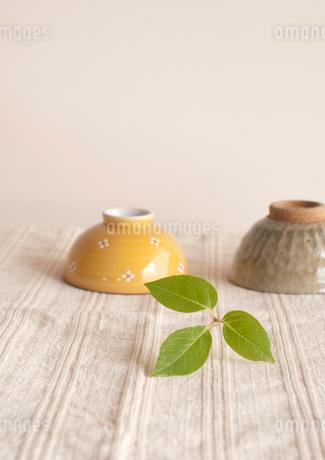 麻布の上に置いた二つの茶碗とグリーンの葉の写真素材 [FYI01946651]