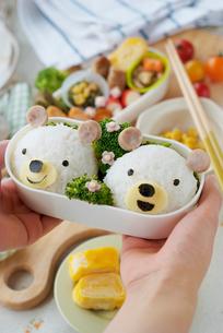 クマのキャラクター弁当を持つ女性の手元の写真素材 [FYI01946752]