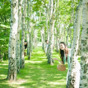 白樺の木の陰から顔を出す男女の写真素材 [FYI01946886]