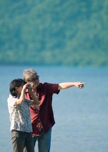 湖で双眼鏡を使い遠くを見るシニア夫婦の写真素材 [FYI01947144]