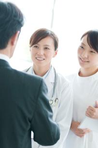 製薬会社の営業マンと話をする女医と看護師の写真素材 [FYI01947199]