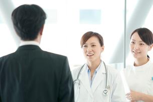 製薬会社の営業マンと話をする女医と看護師の写真素材 [FYI01947243]