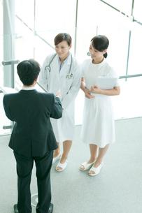 製薬会社の営業マンと話をする女医と看護師の写真素材 [FYI01947252]