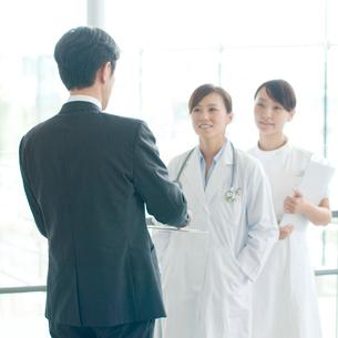 製薬会社の営業マンと話をする女医と看護師の写真素材 [FYI01947348]