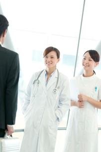 製薬会社の営業マンと話をする女医と看護師の写真素材 [FYI01947350]