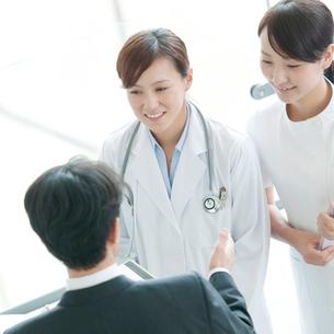 製薬会社の営業マンと話をする女医と看護師の写真素材 [FYI01947363]