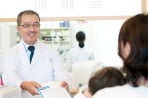 薬を渡す薬剤師と患者の写真素材 [FYI01947395]