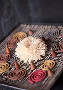 煙の上がった沢山のお香と白い花の写真素材 [FYI01947409]