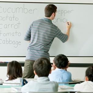 英語の授業をする外国人教師と小学生の写真素材 [FYI01947634]
