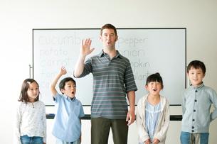ホワイトボードの前に並ぶ外国人教師と小学生の写真素材 [FYI01947643]