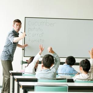 英語の授業をする外国人教師と小学生の写真素材 [FYI01947669]