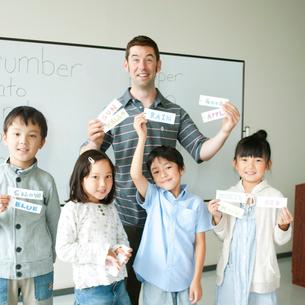 英語の勉強をする小学生と外国人教師の写真素材 [FYI01947685]