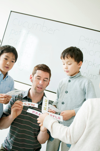 英語の勉強をする小学生と外国人教師の写真素材 [FYI01947689]