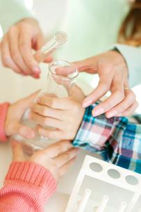 実験をする小学生と先生の手元の写真素材 [FYI01947783]