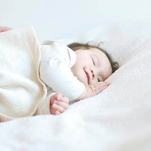 布団の上で微笑む赤ちゃんの写真素材 [FYI01947787]