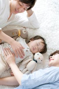 赤ちゃんの寝顔を見守る夫婦の写真素材 [FYI01947788]