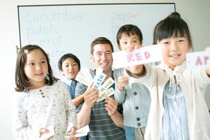 英語の勉強をする小学生と外国人教師の写真素材 [FYI01947793]