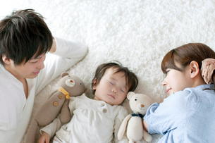 赤ちゃんの寝顔を見守る夫婦の写真素材 [FYI01947795]
