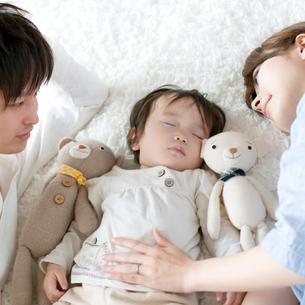 赤ちゃんの寝顔を見守る夫婦の写真素材 [FYI01947805]
