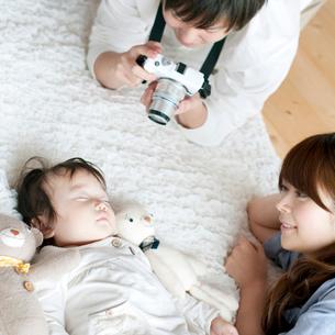 赤ちゃんの写真を撮る夫婦の写真素材 [FYI01947807]