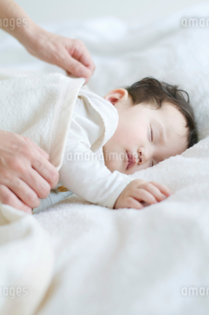 赤ちゃんに毛布をかける母親の手元の写真素材 [FYI01947863]
