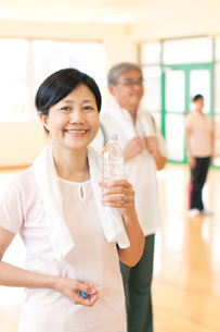 スポーツジムで水を持ち微笑むシニア女性の写真素材 [FYI01947980]