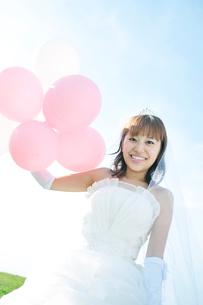 草原で風船を持ち微笑む花嫁の写真素材 [FYI01948012]