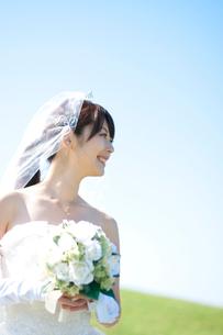 ブーケを持ち微笑む花嫁の横顔の写真素材 [FYI01948065]
