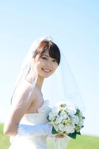 草原でブーケを持ち微笑む花嫁の写真素材 [FYI01948068]