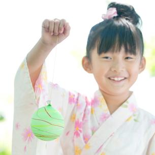 ヨーヨーを持ち微笑む女の子の写真素材 [FYI01948173]