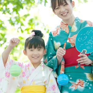 ヨーヨーを持ち微笑む親子の写真素材 [FYI01948183]
