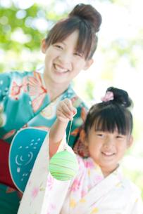 ヨーヨーを持ち微笑む親子の写真素材 [FYI01948185]