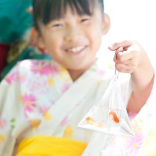金魚の入った袋を持ち微笑む女の子の写真素材 [FYI01948199]