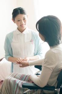 患者の手を握る看護師(訪問医療)の写真素材 [FYI01948259]