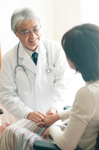 患者の手を握る医者(訪問医療)の写真素材 [FYI01948260]