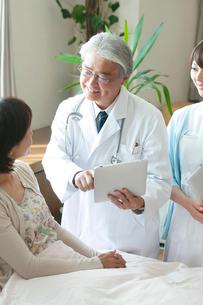 タブレットPCで患者に説明をする医者と看護師(訪問医療)の写真素材 [FYI01948322]