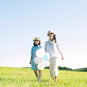 草原で風船を持ち微笑む親子の写真素材 [FYI01948390]