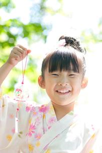 風鈴を持ち微笑む女の子の写真素材 [FYI01948445]