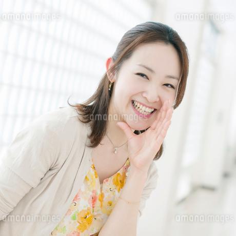 口元に手をあて囁く女性の写真素材 [FYI01948517]