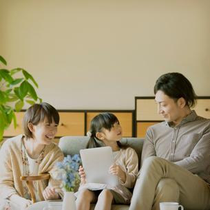 タブレットPCを操作する女の子と見守る両親の写真素材 [FYI01948702]