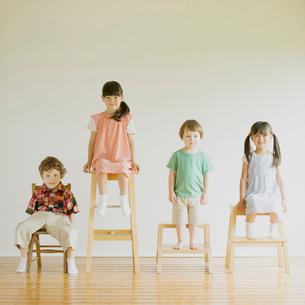 椅子に座り微笑む子供たちの写真素材 [FYI01948752]