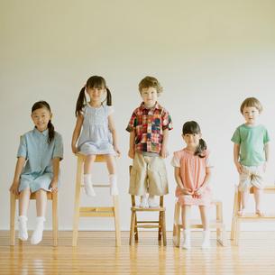 椅子に座り微笑む子供たちの写真素材 [FYI01948757]